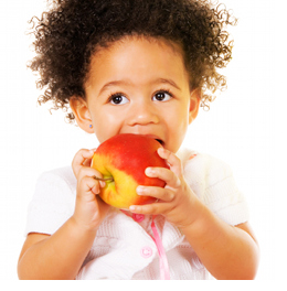 Portrait of a pretty little girl biting an apple